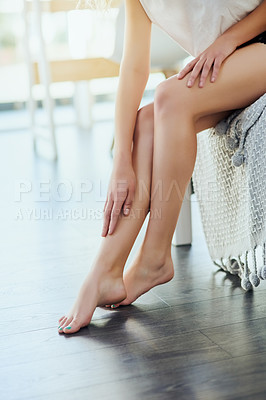 Buy stock photo Cropped shot of an unrecognizable young woman rubbing lotion on her legs while sitting on her bed at home