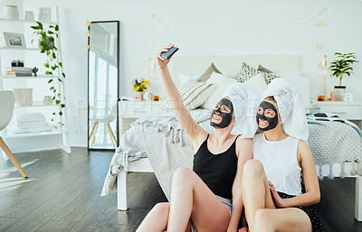 Buy stock photo Cropped shot of two attractive young girl friends taking selfies while pampering themselves at home