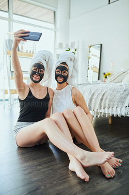 Buy stock photo Full length shot of two attractive young girl friends taking selfies while pampering themselves at home