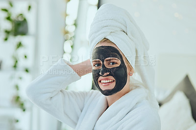 Buy stock photo Cropped portrait of an attractive young woman wearing a face mask while sitting in her bedroom at home