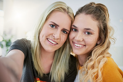 Buy stock photo Shot of a two young friends spending time together at home