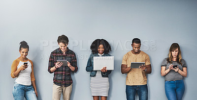 Buy stock photo Studio shot of a group of young people using wireless technology against a gray background
