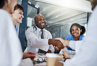 Buy stock photo Shot of doctors shaking hands during a meeting in a hospital