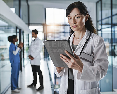 Buy stock photo Shot of a mature doctor using a digital tablet in a hospital with her colleagues in the background