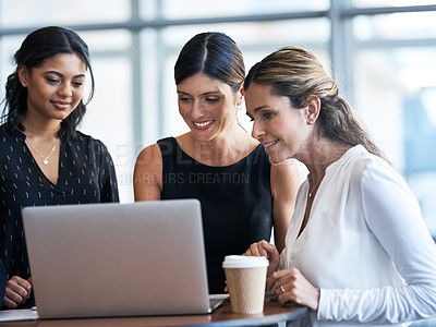 Buy stock photo Shot of a group of businesswomen working together on a laptop in an office