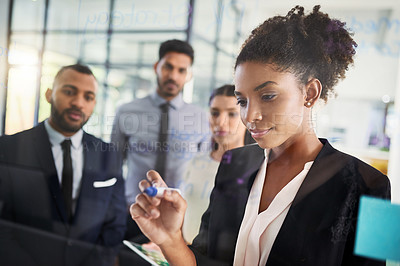 Buy stock photo Shot of a businesswoman writing notes on a glass wall while brainstorming with her colleagues in an office