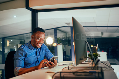 Buy stock photo Cropped shot of a young handsome businessman using a cellphone while working late in the office