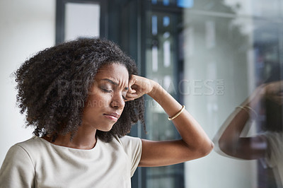 Buy stock photo Cropped shot of an attractive young businesswoman suffering with a headache while standing in her office