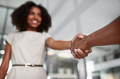 Buy stock photo Low angle shot of two unrecognizable businesswomen shaking hands while standing in their office