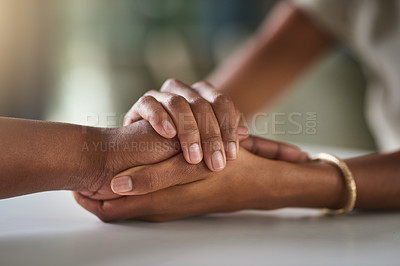 Buy stock photo Cropped shot of two unrecognizable businesswomen holding hands in comfort while sitting in their office