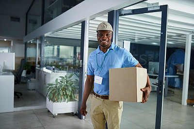 Buy stock photo Portrait of a confident young delivery man holding a box in an office