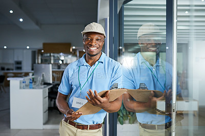 Buy stock photo Portrait of a confident young delivery man holding a clipboard in an office