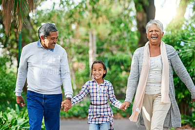 Buy stock photo Cropped shot of an adorable little girl walking hand in hand with her grandparents through the park