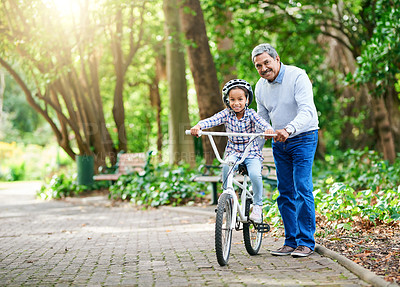 Buy stock photo Full length portrait of an adorable little girl learning how to ride a bike while enjoying the day outdoors with her granddad