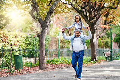 Buy stock photo Full length shot of an adorable little girl riding on her granddad's shoulders while enjoying the day outdoors