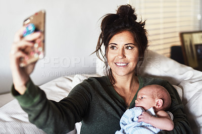 Buy stock photo Shot of a cheerful young woman lying on the sofa while holding her little infant son and taking a selfie at home during the day