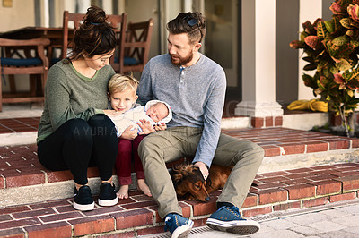 Buy stock photo Shot of a young cheerful family standing together outside at home during the day