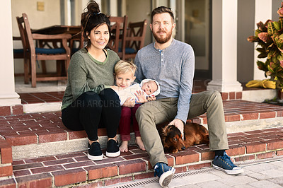 Buy stock photo Portrait of a young cheerful family standing together outside at home during the day
