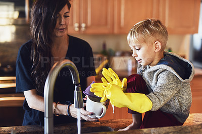 Buy stock photo Shot of a cheerful little boy wearing yellow washing gloves helping his mother do dishes in the kitchen at home