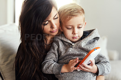 Buy stock photo Shot of a carefree young woman browsing on a cellphone with her little boy while being seated on a sofa at home during the day