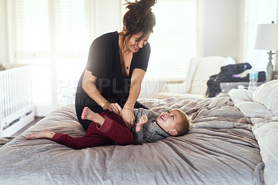 Buy stock photo Shot of a cheerful little boy being tickled by his mother while they both hang out on the bed at home during the day