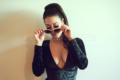 Buy stock photo Shot of a sexy young woman wearing sunglasses while posing against a wall at home
