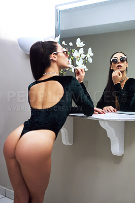 Buy stock photo Cropped shot of a sexy young woman applying lipgloss while looking in the mirror at home