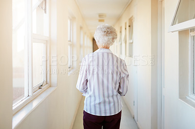 Buy stock photo Rearview shot of a senior woman walking down a corridor in a retirement home