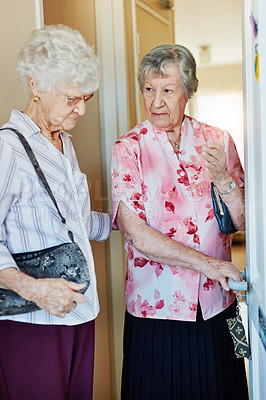 Buy stock photo Shot of two elderly woman closing the door before they leave to go out