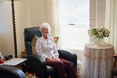 Buy stock photo Portrait of a happy elderly woman relaxing on a chair at home