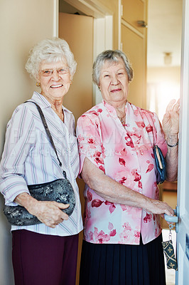 Buy stock photo Portrait of two elderly woman closing the door before they leave to go out