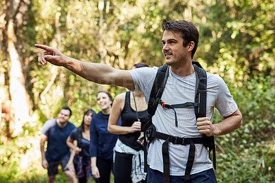 Buy stock photo Shot of a man pointing at something while our hiking with other