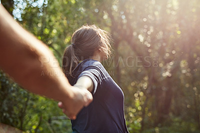 Buy stock photo Cropped shot of a young woman pulling her boyfriend's hand while exploring nature
