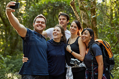 Buy stock photo Shot of a group of friends taking a selfie while out hiking