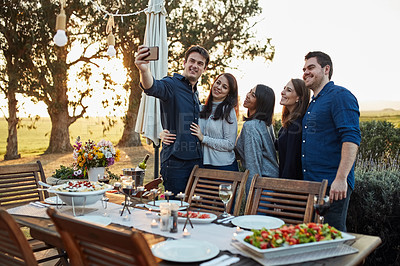 Buy stock photo Shot of a group of friends taking a selfie together outdoors