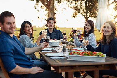 Buy stock photo Portrait of a group of friends making a toast while enjoying a meal together outdoors