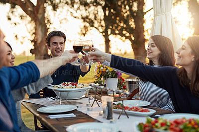 Buy stock photo Shot of a group of friends making a toast while enjoying a meal together outdoors