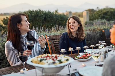 Buy stock photo Shot of a group of friends enjoying a meal together outdoors