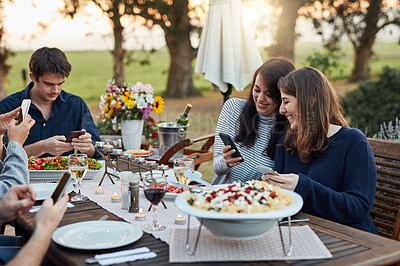 Buy stock photo Shot of a group of friends using their cellphones while having a meal together outdoors