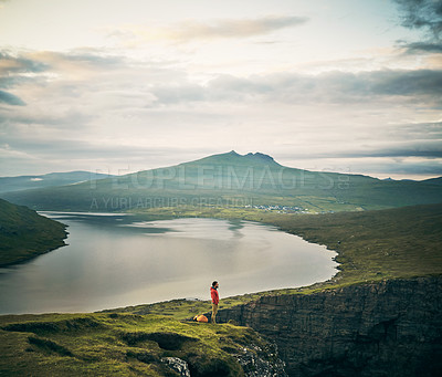 Buy stock photo Shot of a carefree young man standing on the edge of a cliff looking into the distance outside during the late afternoon hours