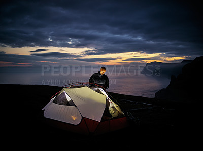 Buy stock photo Shot of a focussed young man putting up a tent outside in nature at night