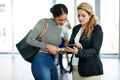Buy stock photo Shot of two businesswomen using a digital tablet together at a convention center