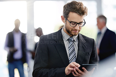 Buy stock photo Shot of a young businessman using a digital tablet at a convention center