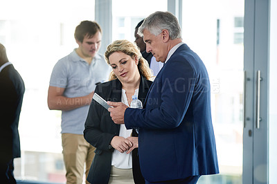 Buy stock photo Shot of a businessman and businesswoman using a digital tablet together at a convention center