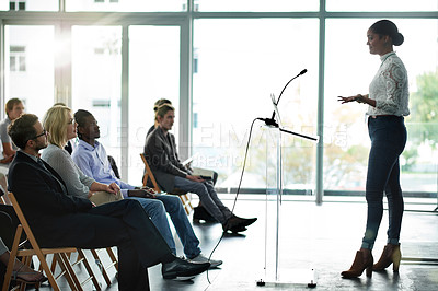 Buy stock photo Shot of a young businesswoman delivering a presentation at a conference