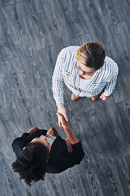 Buy stock photo High angle shot of two businesswomen shaking hands in an office