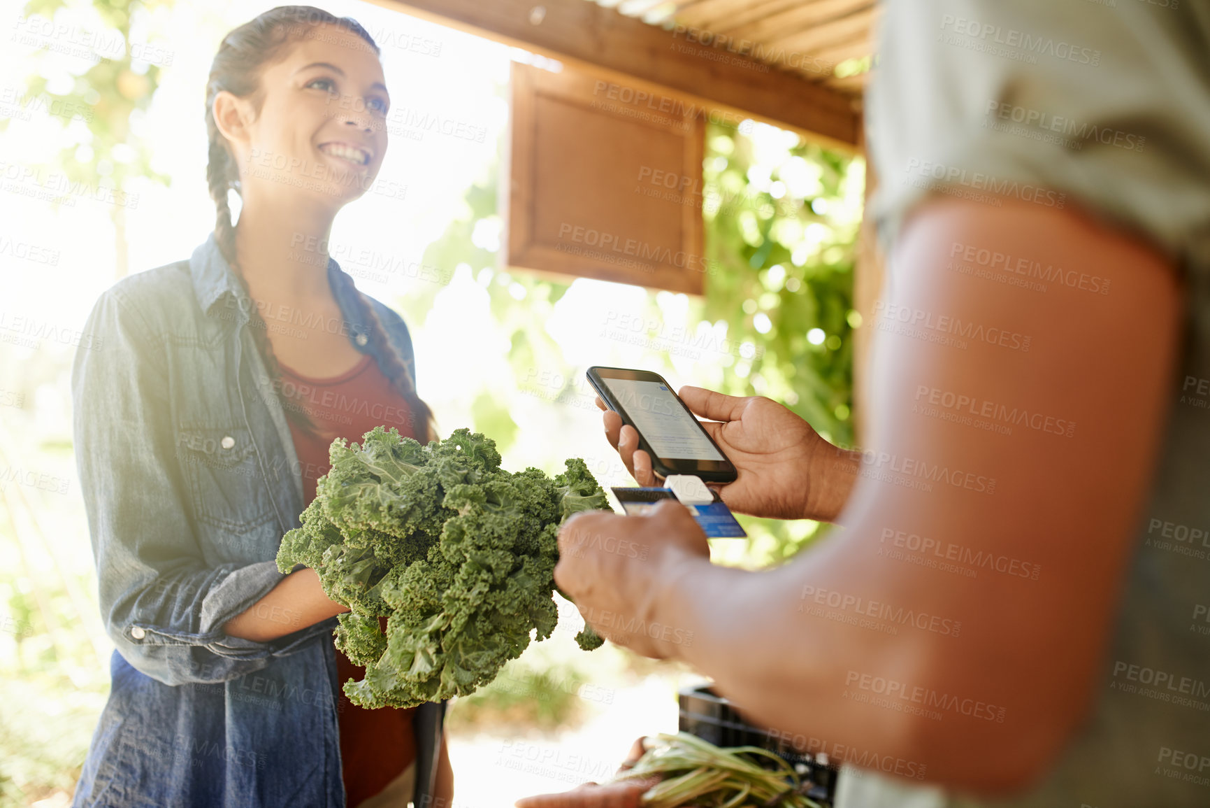 Buy stock photo Cropped shot of an unrecognizable young man taking payment from a female customer at his stall at the farmers' market