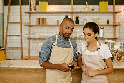 Buy stock photo Shot of two young business owners and partners standing inside of their coffee shop while browsing on a cellphone during the day