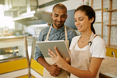 Buy stock photo Shot of two young business owners browsing on a digital tablet together while standing inside of their coffee shop during the day