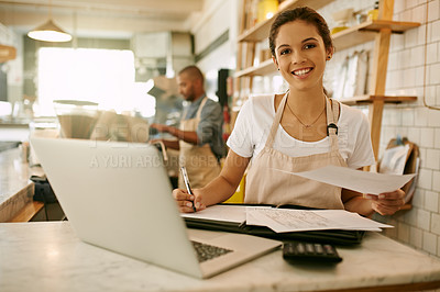 Buy stock photo Portrait of a cheerful young woman working on her laptop while making notes inside of a coffee shop during  the day